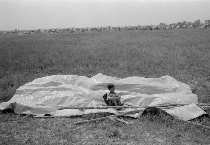 John Vink  CAMBODIA. Anglon Kgnan. 30/11/2001: Relocation of Bassac slums fires victims on former rice fields, 20Km from Phnom Penh. Newly arrived waiting to know where his plot of land will be. Each family is given a tarpaulin and 30 kg of rice.