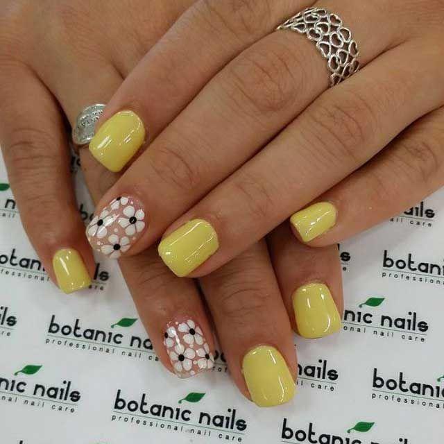 Agradables uñas en color amarillo y beige decoradas con flores blancas y negras y lunares.