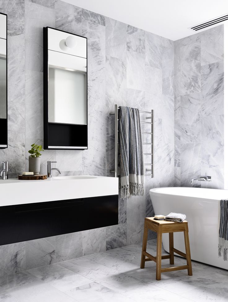 Scandinavian bathroom with marble wall and floor. Brookville apartment by  MA Architects.