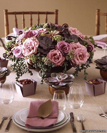 Table arrangements for your wedding in romantic purple and blue hues. In an arrangement that evokes an English garden, roses and flowering oregano in mauve tones contrast with succulents and curly fiddleheads.