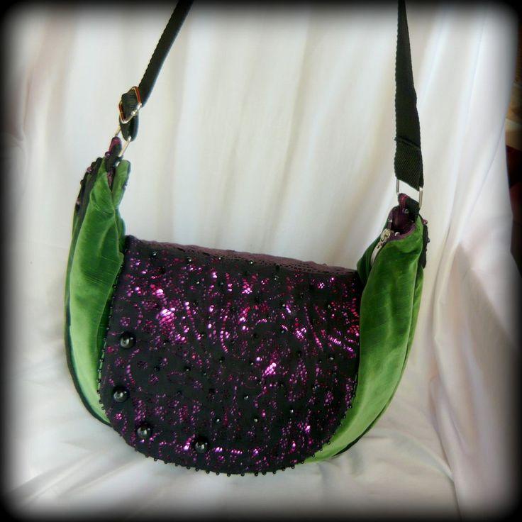 Zöld-lila bohém táska -Handmade by Judy Majoros: Zöld bársony bútorszövet az alapja a táskának. Belsejét szivacsfóliával béleltem, ez tartást ad a táskának, valamint vízállóvá teszi. Felső ráhajtható része lila flitteres anyagból készült, melyet fekete csipkével borítottam, és sok-sok fekete gyönggyel díszítettem. Körben zsinór díszítést kapott. Cipzárral záródik. Belseje lila szaténnal bélelt, és csipkével díszített, valamint 3 zseb található benne.