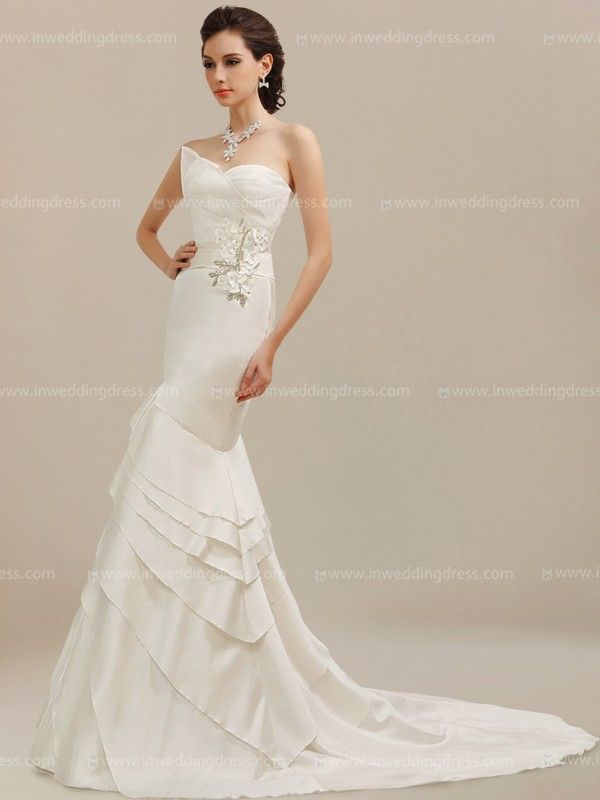 Mermaid wedding dress with strapless asymmetrical neckline is ultra-elegant and feminine. Slim silhouette features fitted Organza front bodice while the flared layered Taffeta skirt finishes off the look. This eye-catching unusual wedding dress style has all the right elements as a perfect wedding gown! Corset back closure and fully lined.