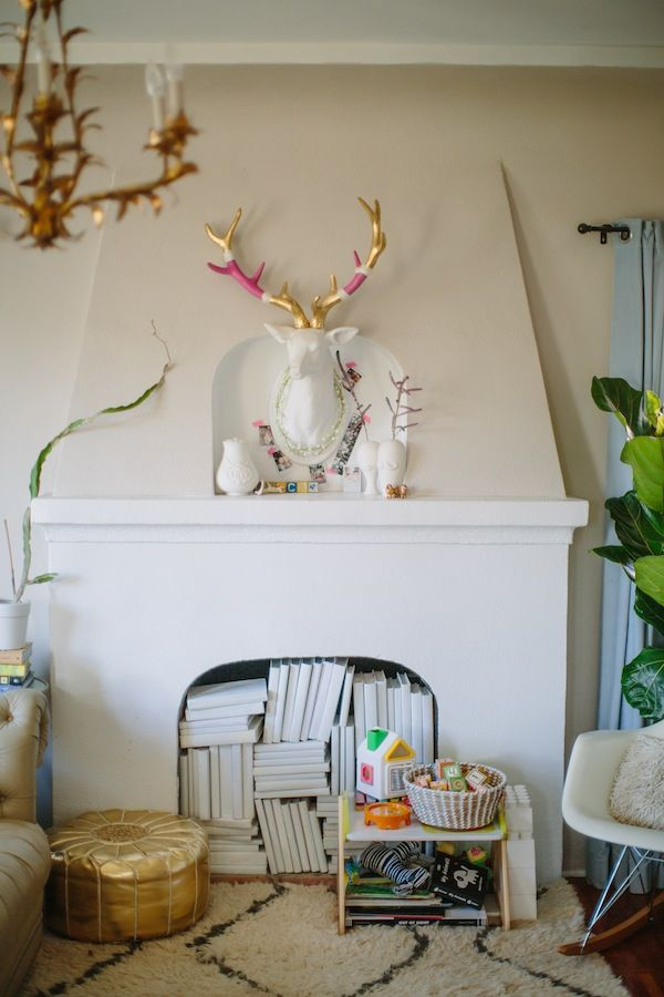 Faux deer head and a fireplace full of books.