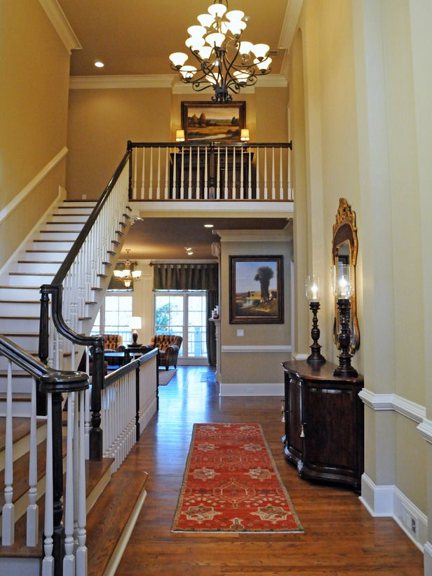 This Neutral Two Story Foyer Shows Off The Staircase, Hardwood Flooring And  A Chandelier. Landscape Art On Both Levels Ties The Two Spaces Together.