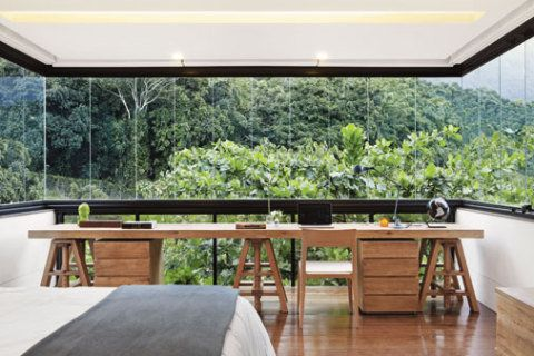 Para preservar ao máximo a vista do Jardim Botânico, a arquiteta instalou apenas uma bancada com cavaletes em frente à janela do quarto do casal. As cortinas podem ser recolhidas no teto. Luminária da Lumini e roupa de cama da Trousseau.