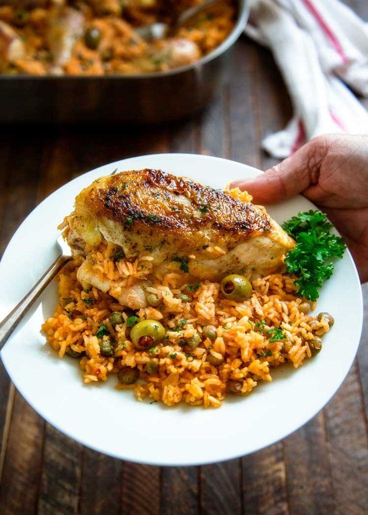 Puerto Rican Chicken and Rice is a Latin classic and packed with flavor, not heat. Browned chicken simmers in rice, flavorful sofrito, olives and capers. @keviniscooking