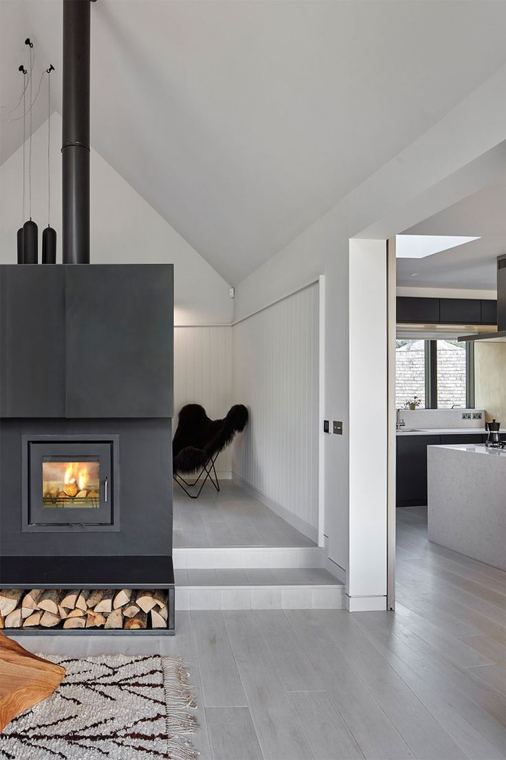 Tucked away behind this steel-clad fireplace with firewood storage is a small library.