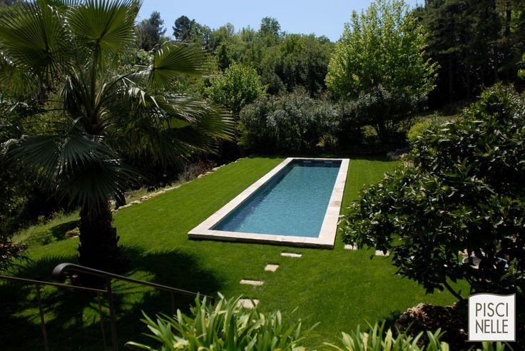 Piscine forme bassin de nage traditionnel | Piscinelle. Piscine en forme de bassin de nage traditionnel équipé d'une belle margelle en pierre naturelle et d'un liner gris ardoise au milieu d'un gazon verdoyant.