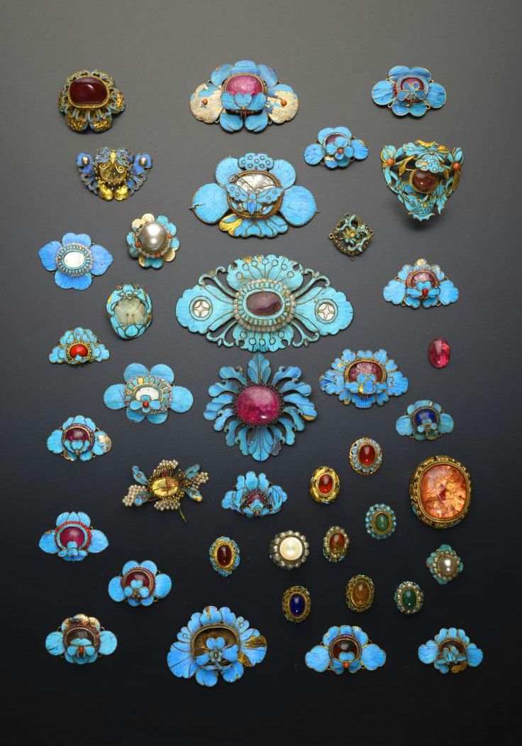 A COLLECTION OF CHINESE GILT METAL AND KINGFISHER FEATHER APPLIQUES, QING DYNASTY (1644–1912), Formed as flowerheads and butterflies, mounted with coloured cabochons and other stones, 9.2cm max. (38)