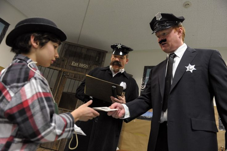 INSPECTION - Connor Casazza, left, receives his passport back after being checked by Scott McCarthy, right, and Bill Briggs who are portraying police officers during White Oak Elementary School's Ellis Island simulation in Westlake Village on Fri., March 1. MC 133