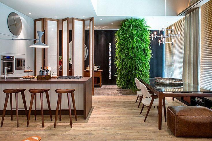 Divisórias pivotantes delimita o hall de entrada do Loft de 100 m² da arquiteta Paola Ribeiro. Também chama a atenção a coluna revestida por samambaias