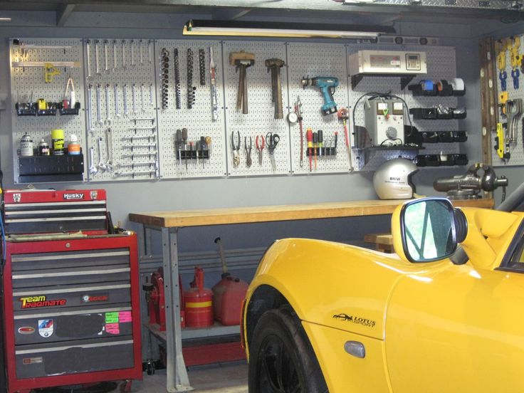 Wall Control gray metal pegboard in race car garage. Metal pegboard storage and organization.