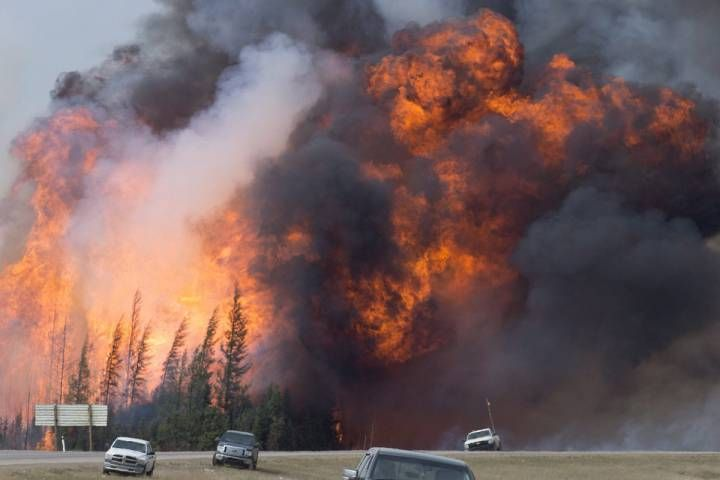 FILE - A giant fireball is seen as a wild fire rips through the forest 16 km south of Fort McMurray, Alberta on highway 63 Saturday, May 7, 2016.