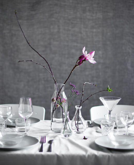 Créez un centre de table en utilisant de simples rameaux, des fleurs et des vases en verre.