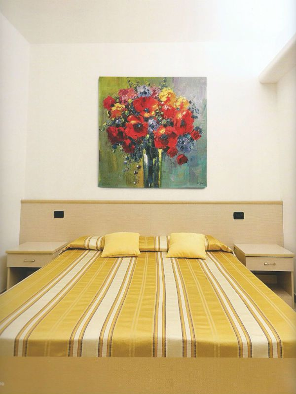 Bob Pejman Poppy Bouquet tapestry shows a glass vase of poppies and other summer flowers. A contemporary Belgian floral wall-hanging