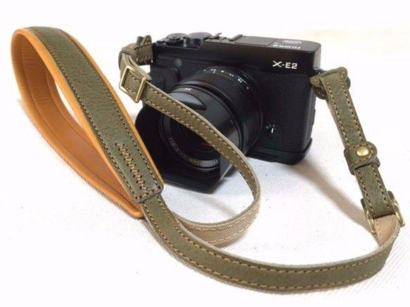 レザー カメラストラップ 色はオリーブです。細身にできてますが、パットの部分はゴムスポンジを軽くて丈夫なホースレザーで包んで身体へのあたりをやわらげてあるのでスマートかつ、柔らかな装着感です。全長126センチで、金具(コキ管)で調節できるのでユニセックスでお使い頂けます。馬の革と薄く丈夫なナイロンを使用している事で、重さが約60gととても軽くできています革でありながら、布製の物と変わらないくらいの軽さです。カメラに取り付ける部分は 厚さ2mm幅11mmになります。 お手持ちのカメラに取り付けられるか、不安な方はお問い合わせください。素材)水牛革、ナイロンテープ、金具
