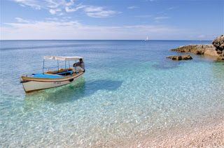 Croatia beach with boat and crystal clear blue waters