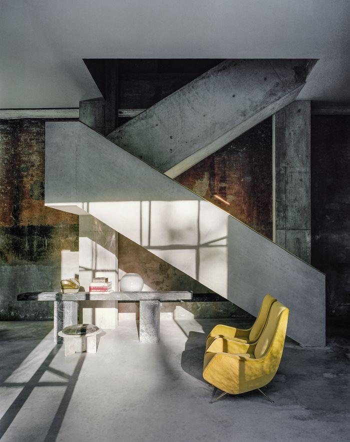 Sous l'escalier en béton, la console est composée de deux marbres différents. Le tabouret en résine recouvert de cuir vieilli est une pièce vintage. Les deux  fauteuils habillés de velours jaune sont signés Aldo Morbelli et datent des années 1950.
