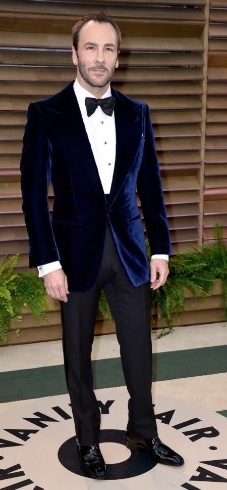 Tom Ford in navy blue velvet dinner jacket with wide, peaked lapels, big studs and cummerbund