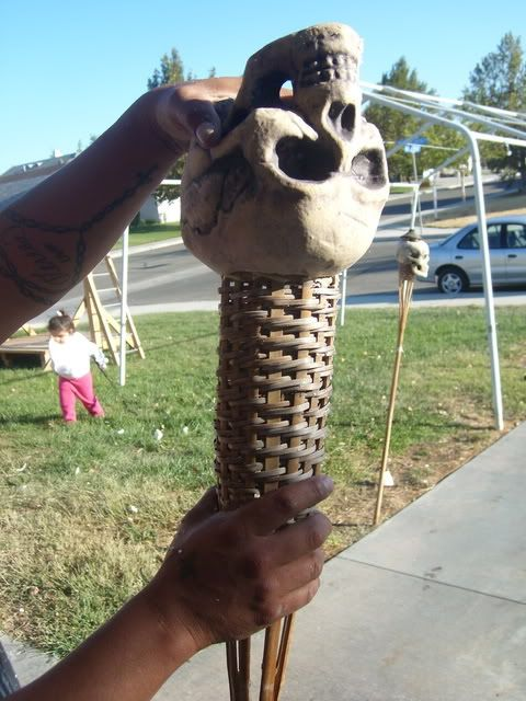 http://www.halloweenforum.com/tutorials-and-step-by-step/73134-making-skull-torches-out-basic-tiki-torch.html