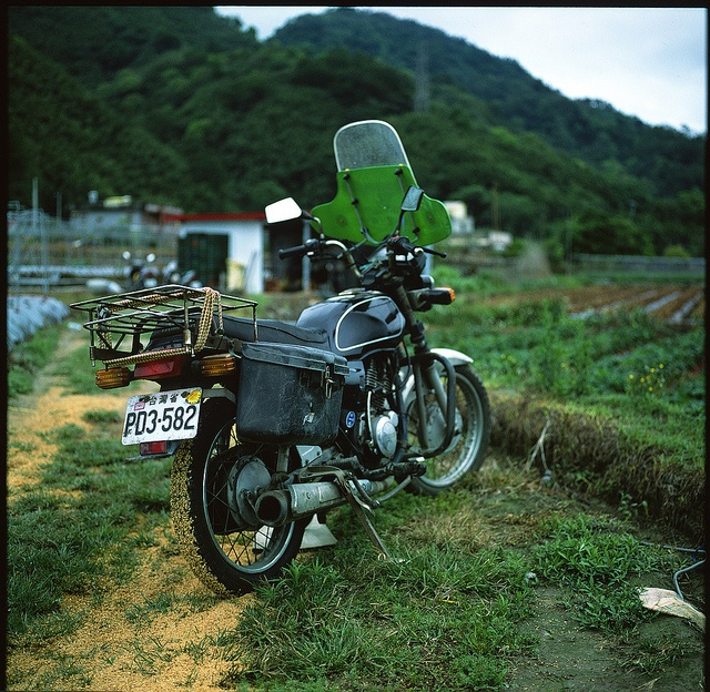 The venerable Yamaha motorcycle with an extra side stand on the right, used by many farmers in Taiwan.