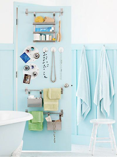 small bathroom storage. Door storage. A light blue bathroom features a door covered in magnetic paint. The surface holds small magnetic hooks and keeps metal towel bars and containers from knocking around.