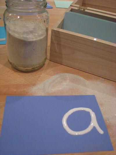 Letters van zand. Schrijf met lijm een letter en strooi er zand overheen