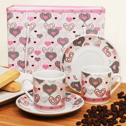 """Take a trip to Italy with one of our magnificent espresso sets! Ruby Blanc's """"Espresso per Due"""" espresso set is a brilliant gift for a variety of occasions and special events. This porcelain espresso set features a pair of cups and saucers decorated with beautiful red, pink and gray hearts secure..."""