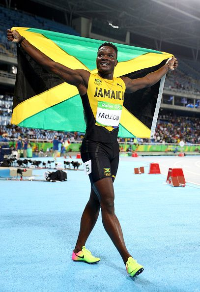 Omar Mcleod of Jamaica celebrates with the flag of Jamaica after winning the…