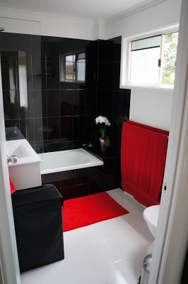 sorta this idea one black wall the rest white black accessories and a black and white shower curtainmaybe red rugs and a couple of red decorations on - Red And White Bathroom