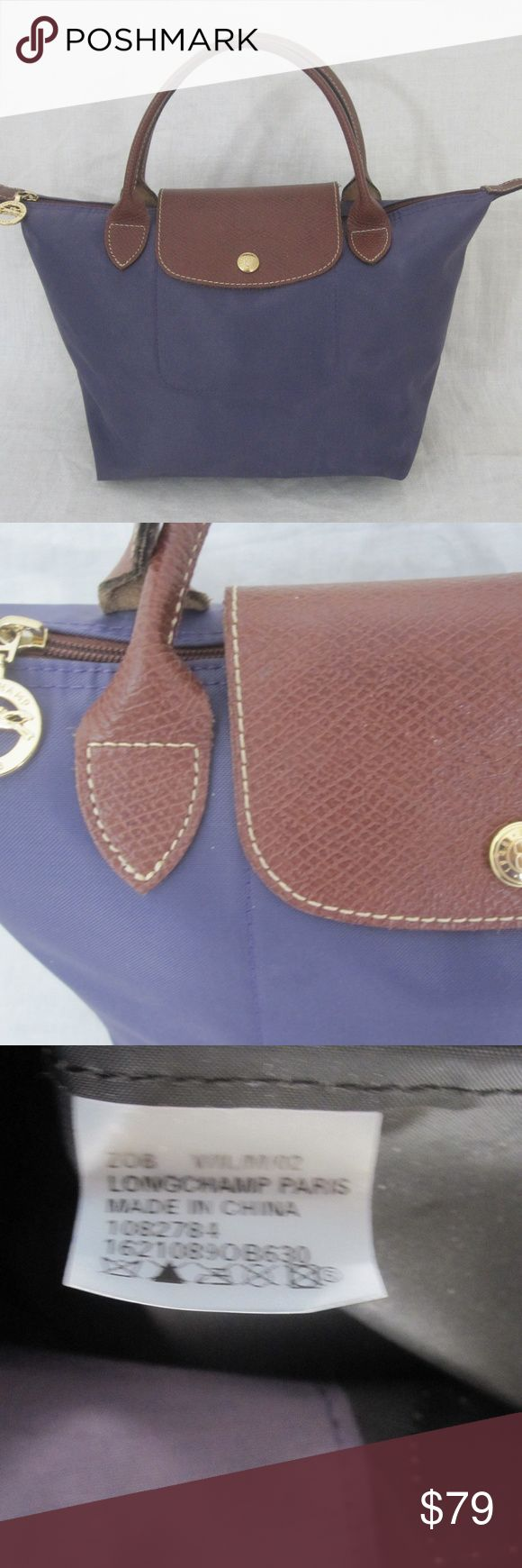 """LONGCHAMP PURPLE LE PLIAGE MODELE DEPOSE HANDBAG THIS IS A NICE LOOKING LONGCHAMP PURPLE CANVAS & LEATHER TRIM   LE PLIAGE MODELE DEPOSE HANDBAG. IT IS 100% AUTHENTIC.  THIS NICE LOOKING BAG WAS PRE OWNED, AND IT'S IN VERY GOOD CONDITION.   THERE ARE NO MAJOR FLAWS TO REPORT, SEE PICTURES.   THE BAG HAS A VERY FEW SMALL MARKS ON THE BODY FROM LIGHT NORMAL WEAR.  AND THERE ARE A FEW DOT MARKS ON THE INSIDE, SEE PICTURES. (HARD TO SEE)  THE BAG MEASURES APPROX: 12""""L X 8""""H X 6""""W, THE HANDLE…"""