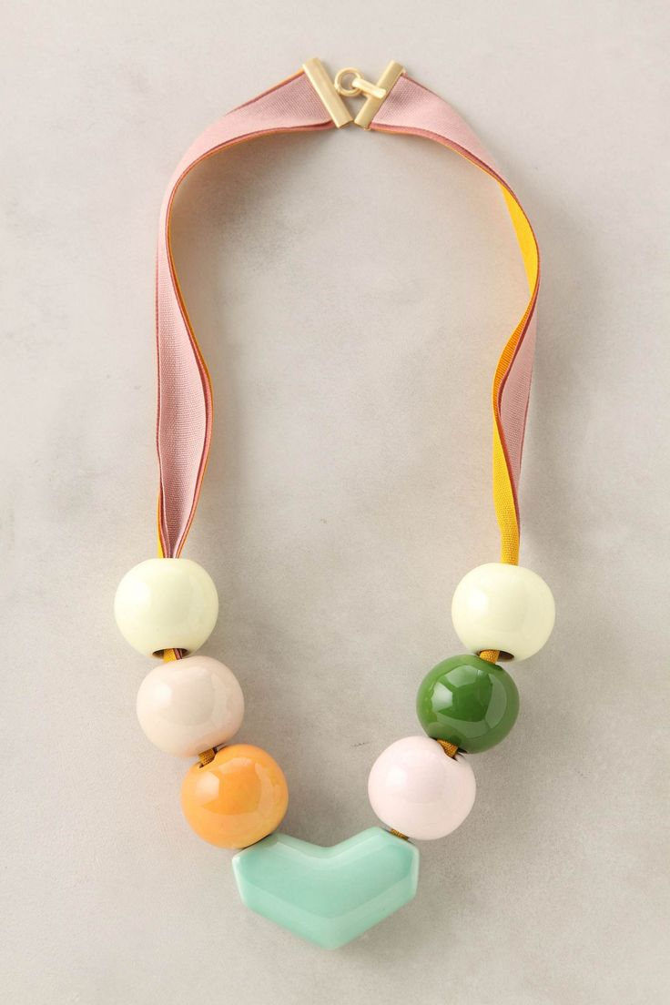 Glazed beads and a gentle heart were handcrafted from glazed ceramic and slung from pretty ribbons by designer Marion Vidal.