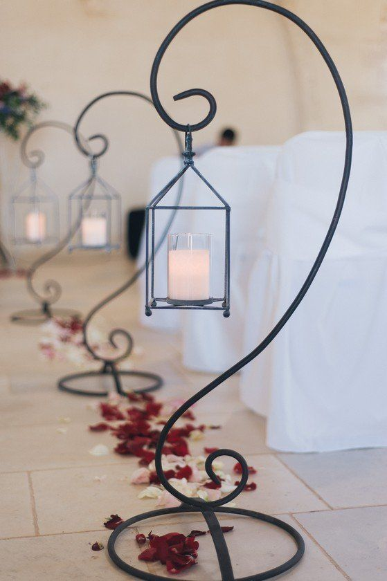 Modern wedding lanterns surrounded by red rose petals