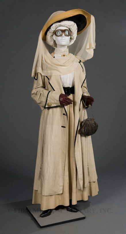 Edwardian Motoring Duster w/goggles.  c 1910-1915      Open cars still created dusty dirty atmospheres and country roads were often unmade.    Loose topcoats in leather, or special motoring coats acted as protection from weather and cold. Oil smuts could be a problem so women wore thick face veils with their hats and even goggles.