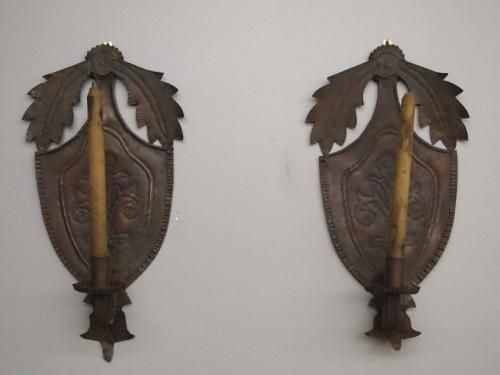 A pair of 19th century tin candle sconces. Shield form bodies with crimped edges and floral punchwork decoration under two foliate swags, each with a single sc