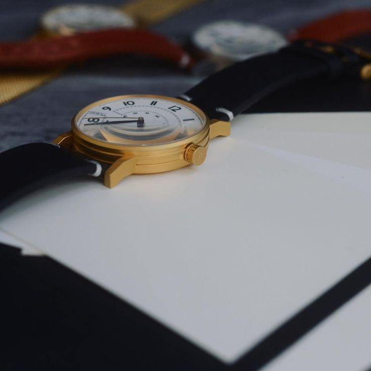 Hirwill Watches. Unique gold case with black leather strap on moleskin.