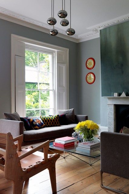 In the sitting room of decorative artist Bridie Hall's house Ikat and Kelim cushions, and yellow and red accents add a burst of colour to the blue/grey paint