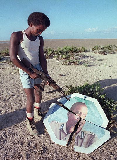 1991. A rebel militiamen during the height of the Somali civil war in short shorts and white tank top.