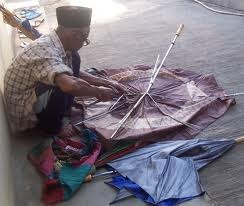 old man and broken umbrella to be repaired..