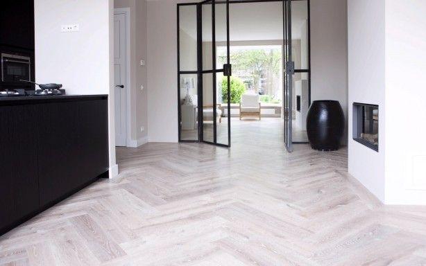 Lichte houten vloer met donkere keuken, hoge plint en stalen binnenkozijnen
