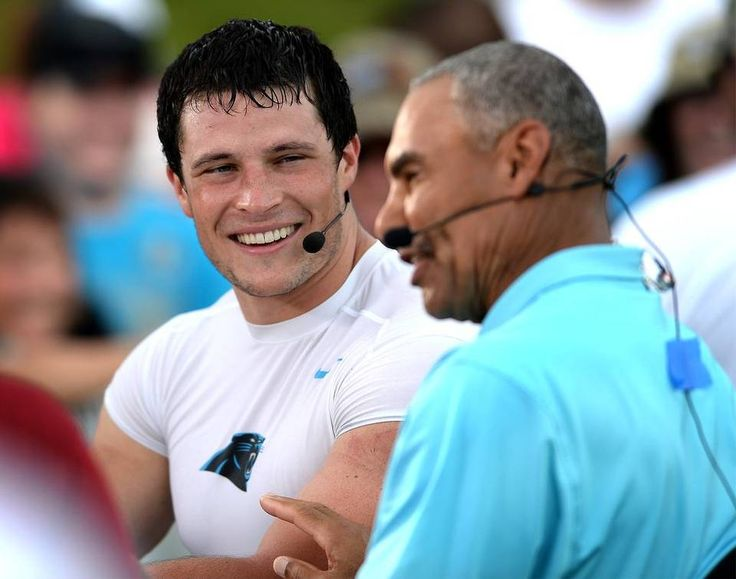 Carolina Panthers linebacker Luke Kuechly, left, smiles as he listens to former NFL player/coach and current ESPN football analyst Herm…