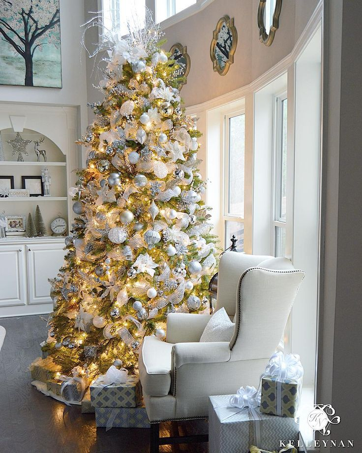 9 foot White, Gold, and Silver Christmas Tree, filled with ornaments in two story great room in front of bow of windows. Check out all the silver and gold Christmas inspiration in this home tour on KELLEYNAN.com