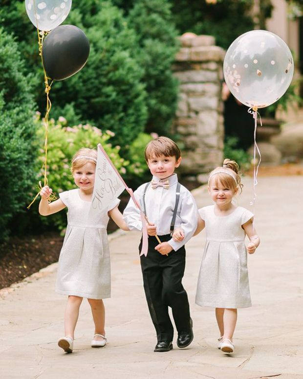 Flower girls and page boy with here comes the bride balloons