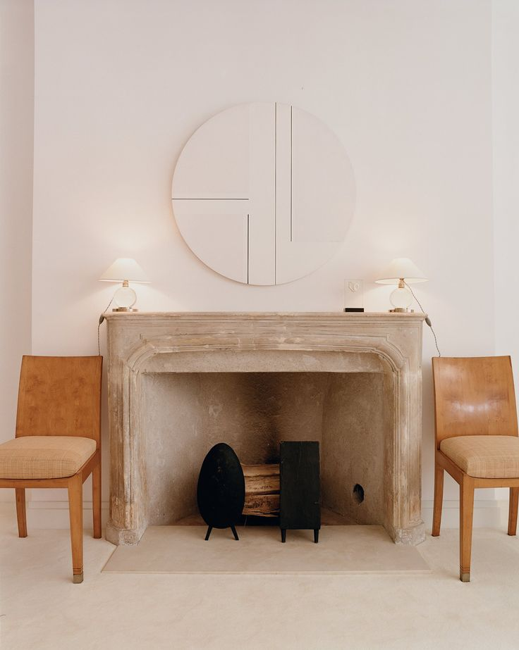 Flanking the 18th-century stone mantel in the master bedroom of Reed Krakoff and wife Delphine's Manhattan brownstone are a pair of chairs by Jean-Michel Frank.