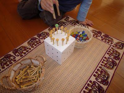 Cvičení na jemnou motoriku: do polystyrénu dětským kladívkem zatlučená golfová týčka a do nich dítě kleštěmi na grilování nebo velkou pinzetou skládá barevné vzory z bambulek, skleněných kuliček, apod.