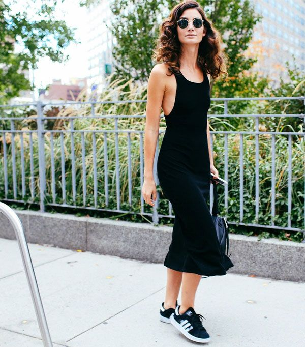 Look Lily Aldridge com vestido preto midi e tênis Adidas.