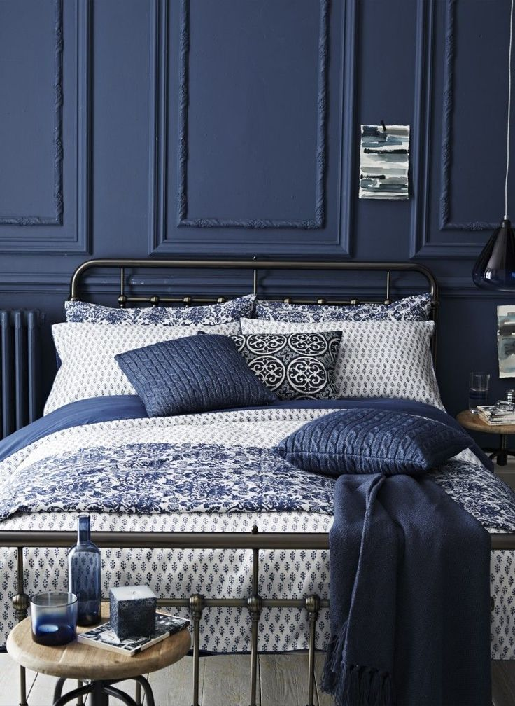 liking the metal bed, dark blue walls and light bedlinen