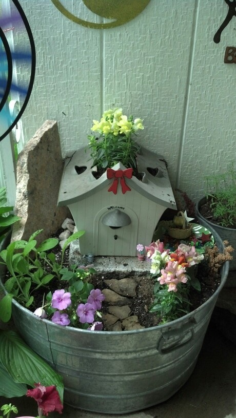 Check out this adorable fairy garden using a full size bird house and large tin bucket as a container.  Great idea for an outdoor all weather fairy garden.