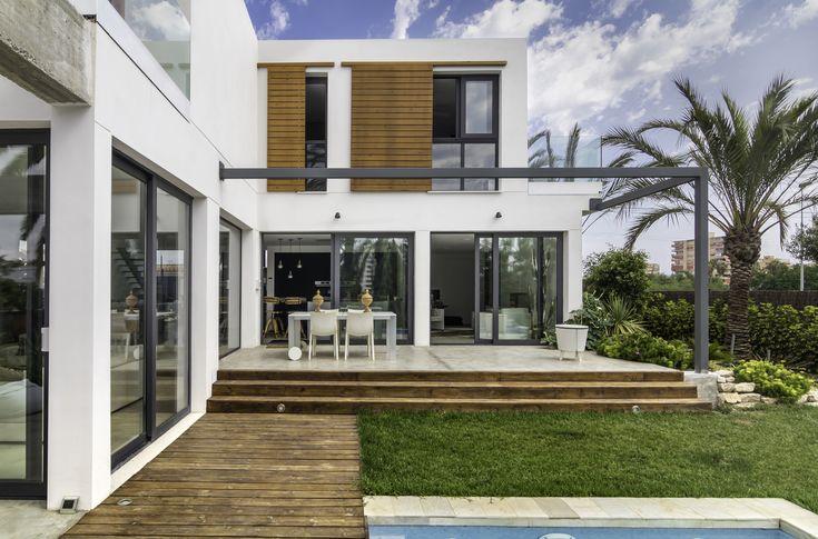 #Fachada de #monocapa con grandes #ventanales en #aluminio #gris #antracita  y con #persianas de #madera #móviles
