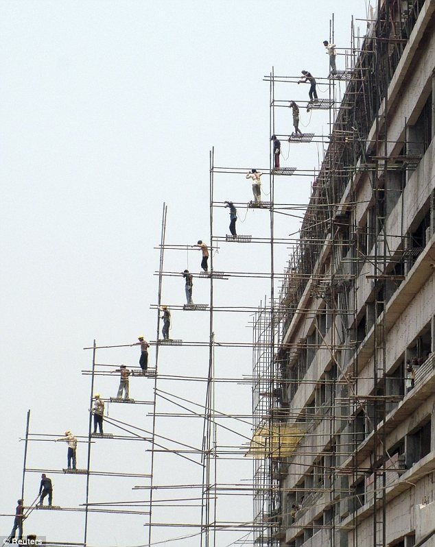 Workers pass poles to one another to put up scaffolding for a new shopping mall in Bhubaneswar, India.  I am glad I don't have to work at that jobsite.